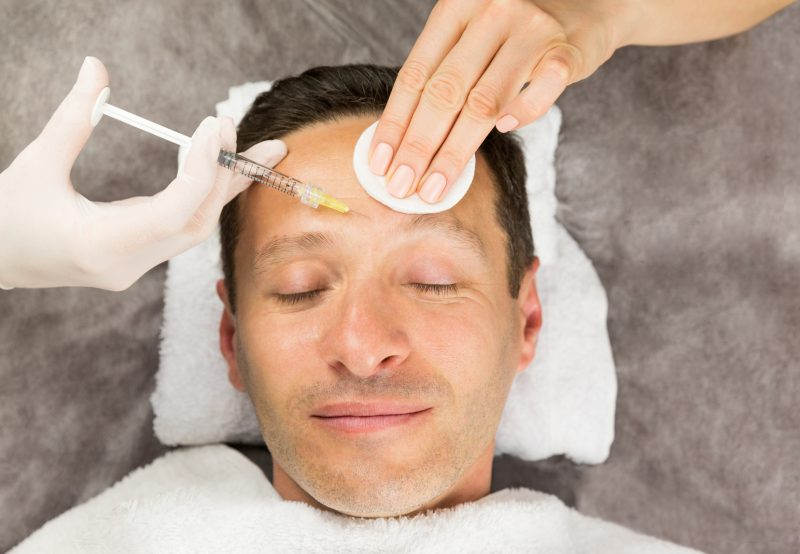 Face of laying man, hands of beautician with a syringe and sponge, horisontal